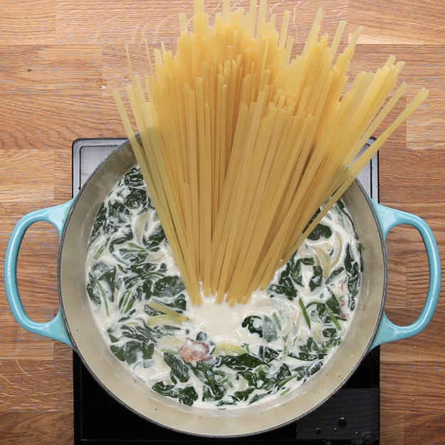 4 servingsINGREDIENTS6 strips bacon, sliced2  chicken breast, sliced2 teaspoons salt1 teaspoon pepper1 teaspoon garlic powder2  onion, sliced4 cloves garlic, minced140 g (5 oz) spinach1.2 L (5 cups) milk455 g (1 lb) fettuccine110 g (1/2 cup) pesto110 g (1 cup) parmesan cheese parmesan cheese, for garnish fresh parsley, for garnishPREPARATION1. In a large pot or dutch oven over medium-high heat, cook the bacon until crispy.2. Add chicken and season with salt, pepper, and garlic powder. Cook until no pink is showing, then remove the chicken.3. Add onion and garlic and cook until softened.4. When onions are caramelized, add spinach and cook until wilted5. Add milk and bring to boil.6. Add fettuccine into boiling mixture and cover.7. Cook fettuccine on medium heat until milk thickens and pasta is cooked (about 7 minutes).8. Mix back in the chicken. Stir in the pesto and parmesan.9. Garnish with parsley and additional parmesan10. Enjoy!