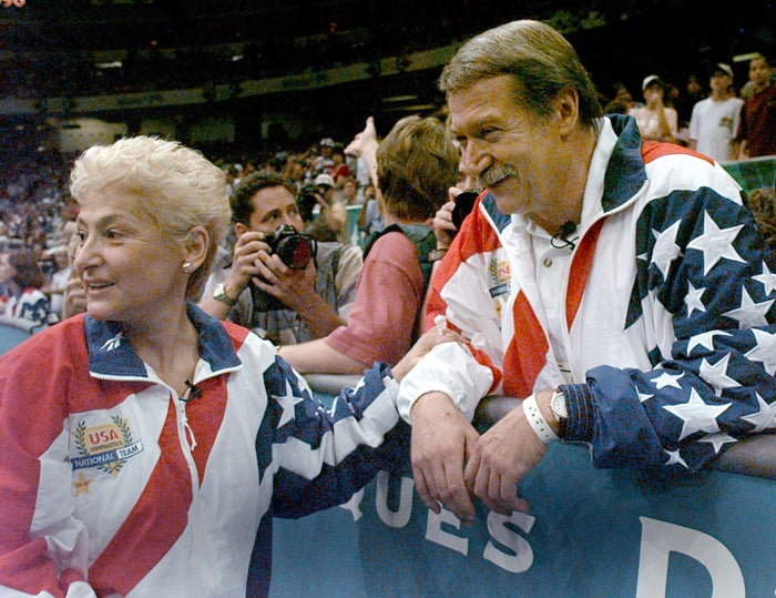Martha and Bela Karolyi watch as the US women's gymnastics team celebrates winning the gold medal at the Centennial Summer Olympic Games in Atlanta.
