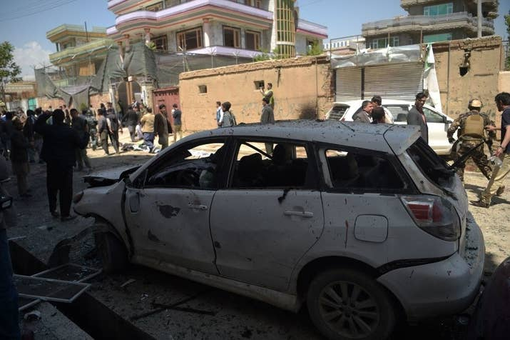 Afghan residents inspect the site of a suicide bombing outside a voter registration center in Kabul on April 22, 2018.