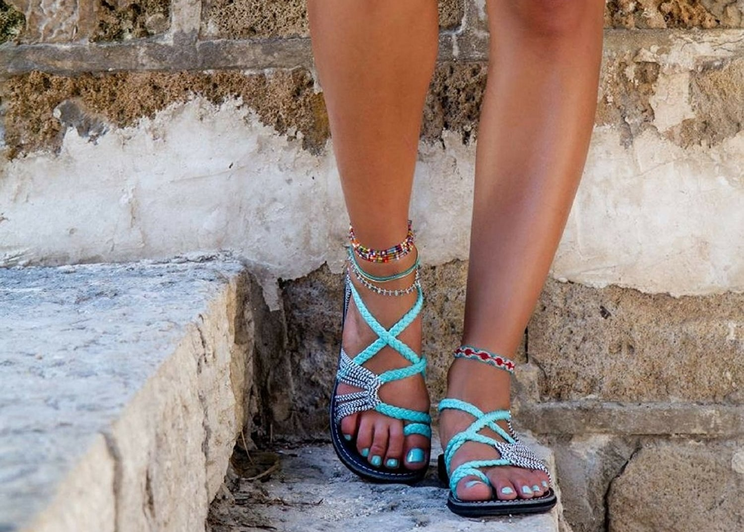 A model wearing the Plaka Sandals in Turquoise-zebra