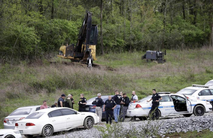 Police gather on a road in a wooded area near where Waffle House shooting suspect Travis Reinking was captured.