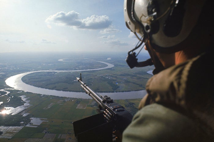 A machine gunner scans for hostiles while his helicopter is on patrol over the Mekong Delta.
