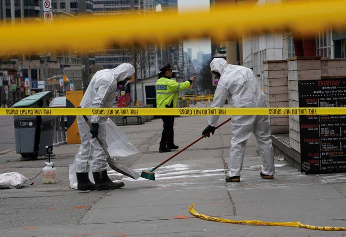 A work crew in protective clothing cleans a sidewalk a day after a van struck multiple people along a major intersection in north Toronto.