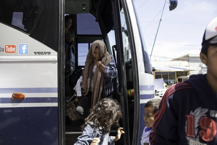 Women and children from the migrant caravan exit a bus in Mexicali, where they were given food, rest and medical attention, if they needed it.