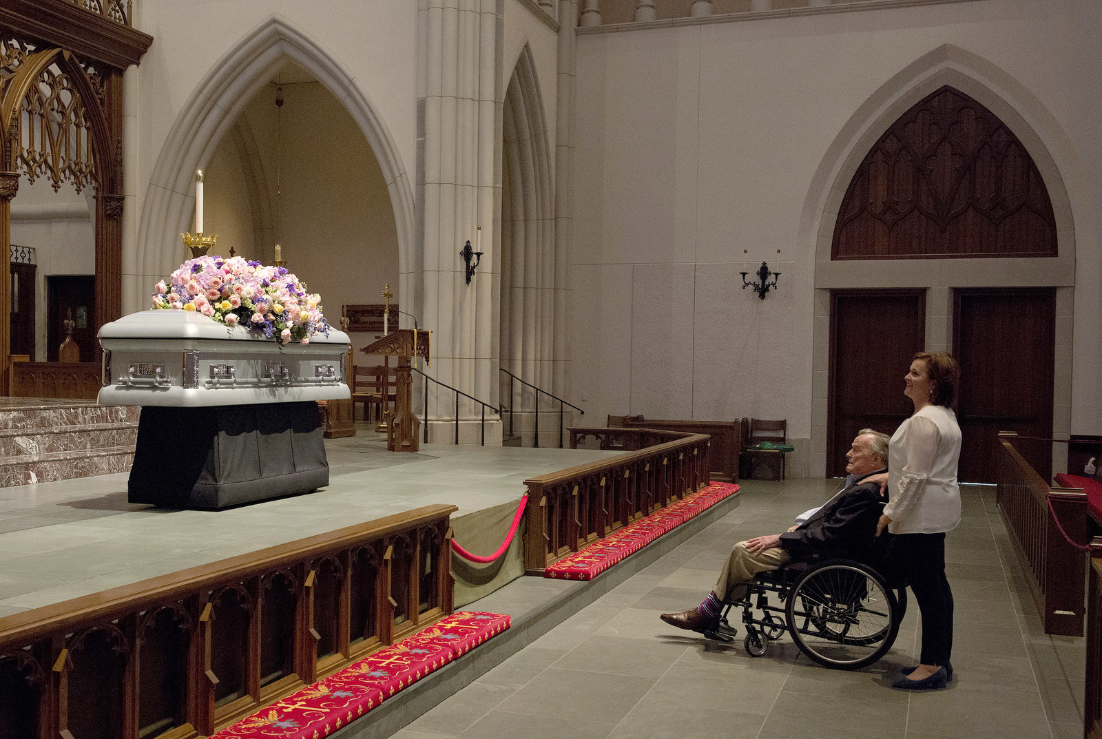 "Bush looks at the casket of his late wife with his daughter Dorothy ""Doro"" Bush Koch on April 20."