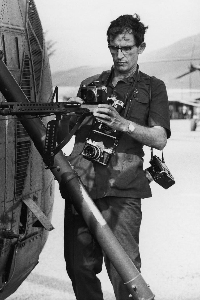 Larry Burrows attaching cameras to the Yankee Papa 13 helicopter prior to a mission during the Vietnam War.