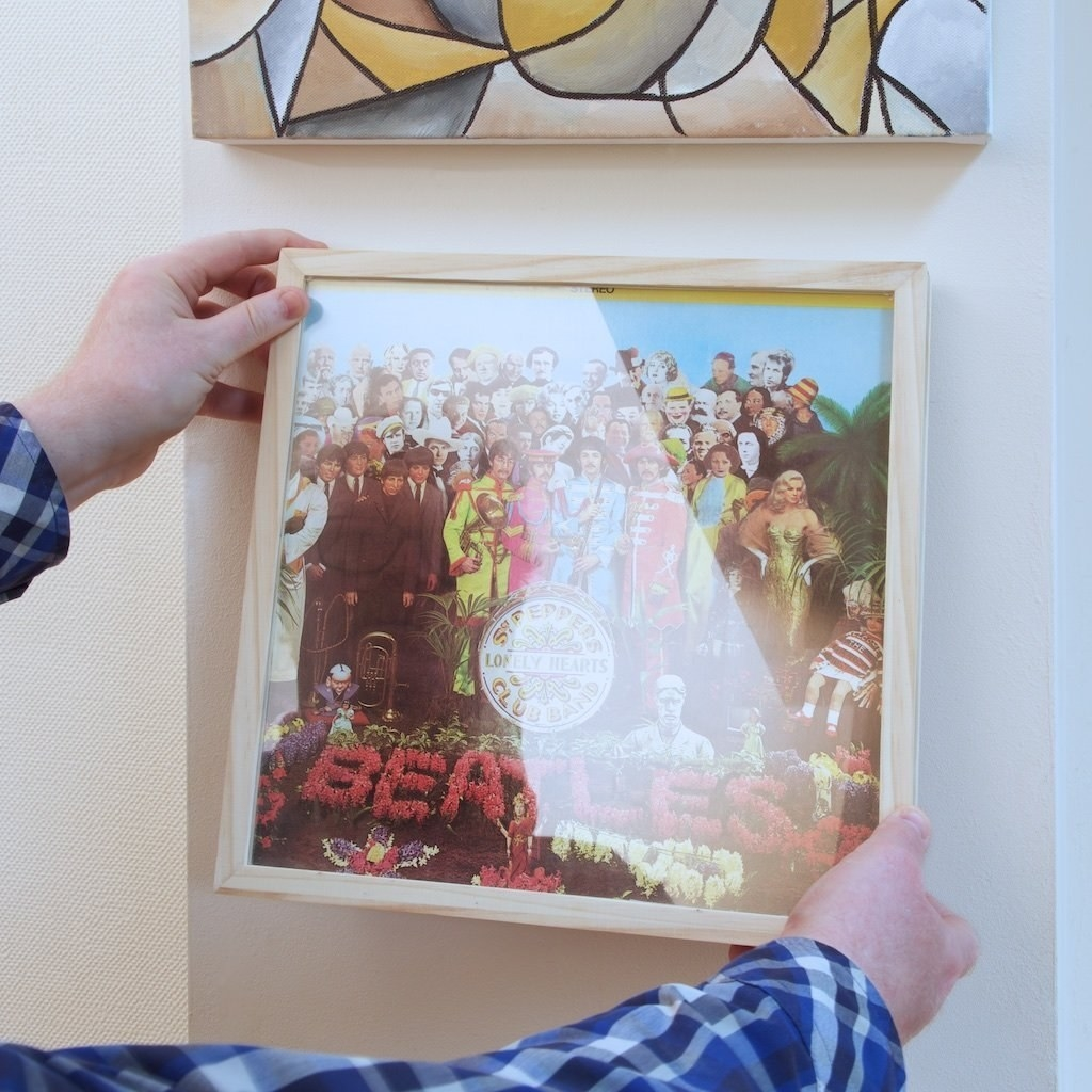 a model hangs up a wooden frame with a beatles record in it