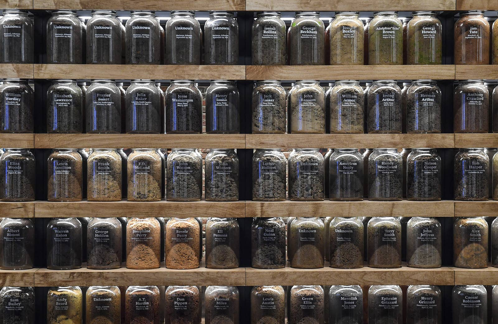 Soil samples from lynching sites across the country are displayed at the Legacy Museum. Each sample of soil has a date of a lynching and the name of the person lynched. On some samples, the jars are marked with Unknown if the names were not known.