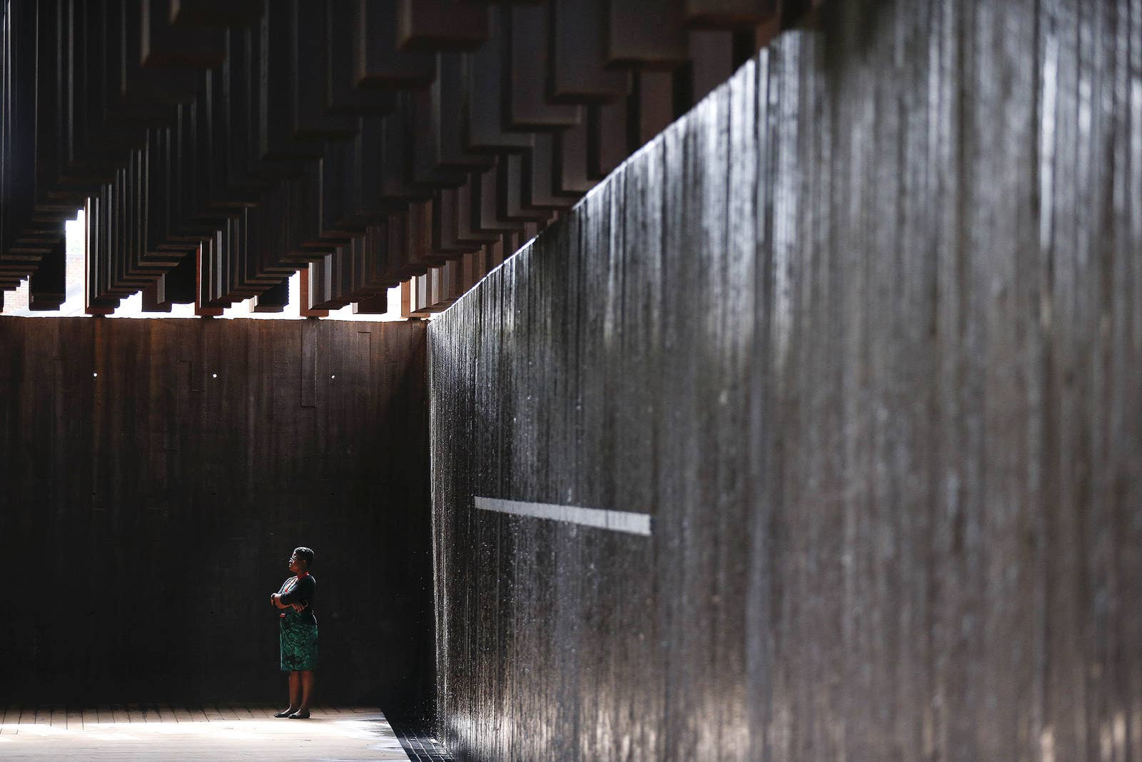 A visitor to the memorial stands in reflection amid the steel monuments above.