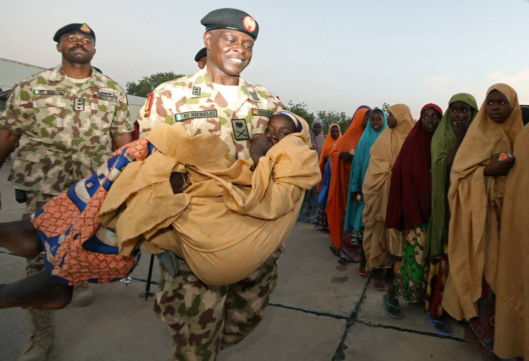 Major General Rogers Nicholas carries one of the newly released Dapchi schoolgirls as others wait to board a plane at the air force base in Maiduguri, Nigeria.