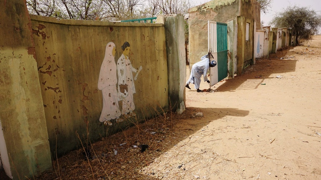 A watchman opens the gate of the deserted student boarding section of the school in Dapchi.
