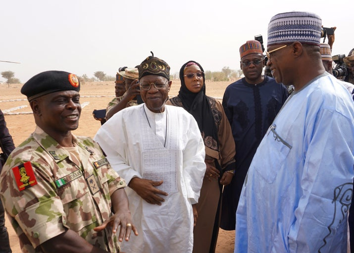 Yobe State Governor Ibrahim Gidan (right) speaks with Information Minister Lai Mohammed and the head of the military force fighting Boko Haram, Major General Rogers Nicholas, on the premises of the school after the girls were abducted.