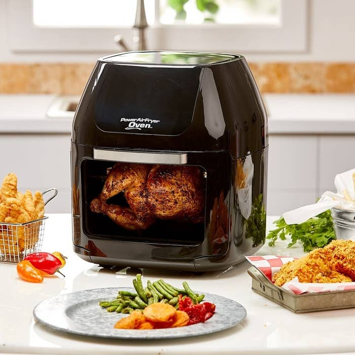 """Promising review: """"I cook EVERYTHING in it. Almost anything I would cook in my oven, I can cook in the Air Fryer in half the time. I cooked biscuits this morning and tested cooking half in a pre-heated oven and half in the fryer and the fryer cooked in half the time and didn't heat up the kitchen like the oven does. I've also noticed that my electric bills have been substantially lower since my purchase of the item as I never use my oven anymore. It cooks the best chicken wings and fried chicken without the extra grease. I skin the chicken and flour with seasoned flour, mist it lightly with corn oil or olive oil and Voila! Perfect fried chicken in about 15–20 minutes. I love the trays so I can cook more at one time. It also cooks amazing artisan-like pizza that tastes like it came out of a pizza oven."""" —Carrie S.Get it from Amazon for $169.99+ (available in four colors)."""