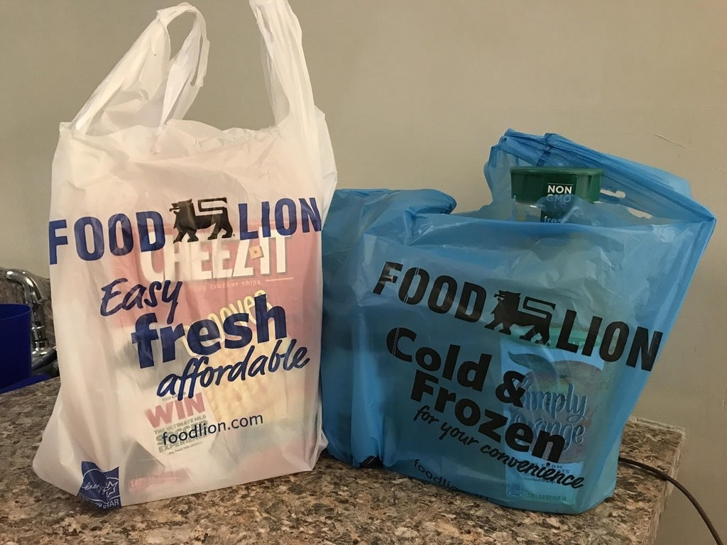 "Two grocery bags, one white and one blue. The blue one says ""cold and frozen."""