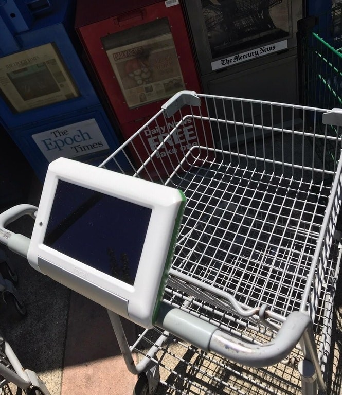 A grocery cart with a tablet on the handle