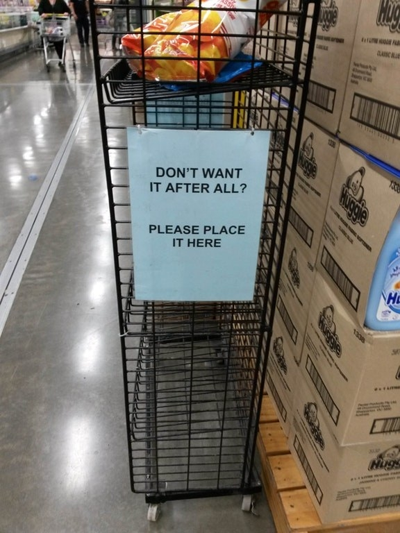 A shelf with a sign that reads: Don't want it after all? Please place it here