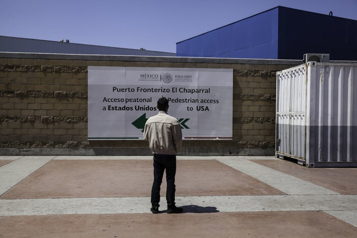 Noel, a teenager from Honduras, looks at the sign pointing to the United States from Tijuana.