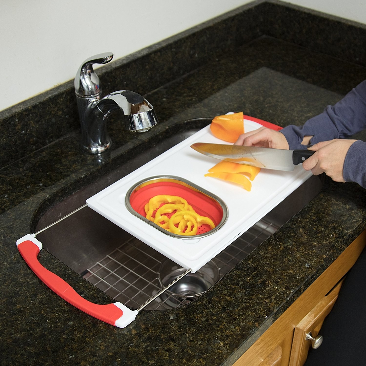 The cutting board with peppers being chopped on it and rinsed in the silicone strainer