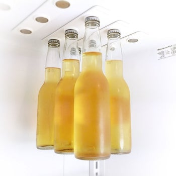 four glass bottles hanging from the top of the fridge