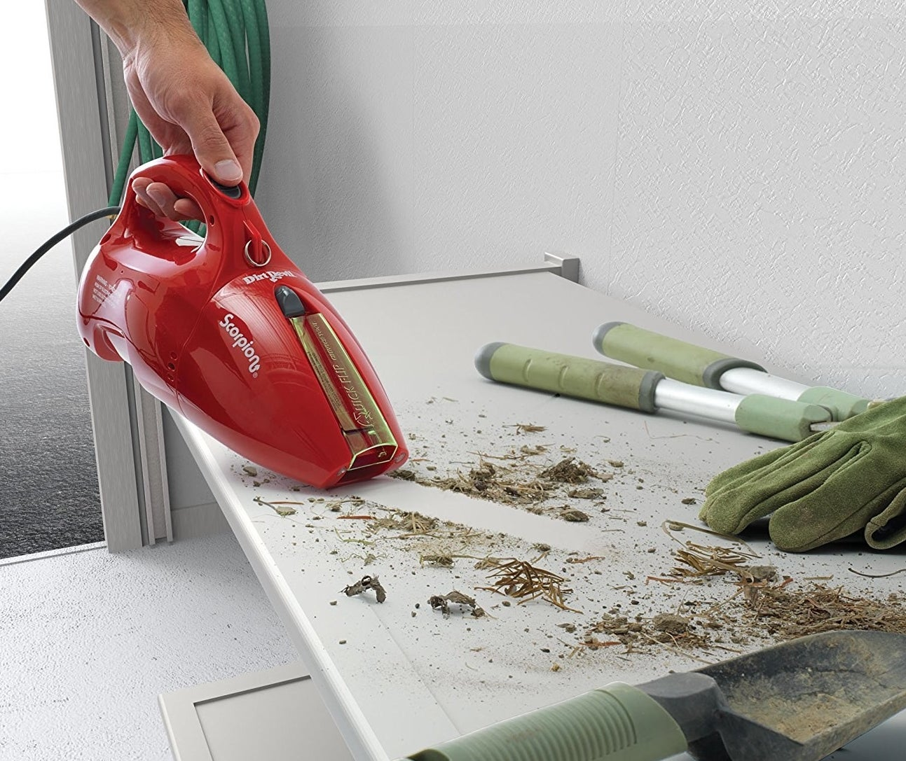 small red vacuum sucking up spilled dirt