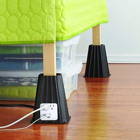 Black, pyramidal leg lifts raising a bed with storage bins underneath. One lift has two outlets and a USB plug with a power cord running from it