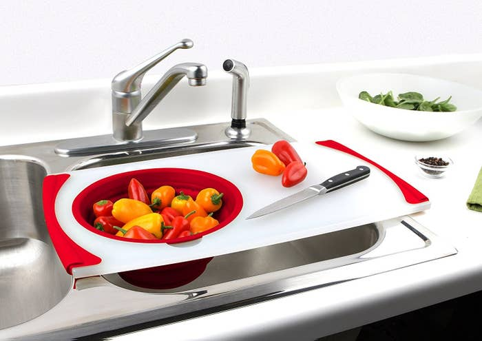A chopping board with strainer built in placed over sink
