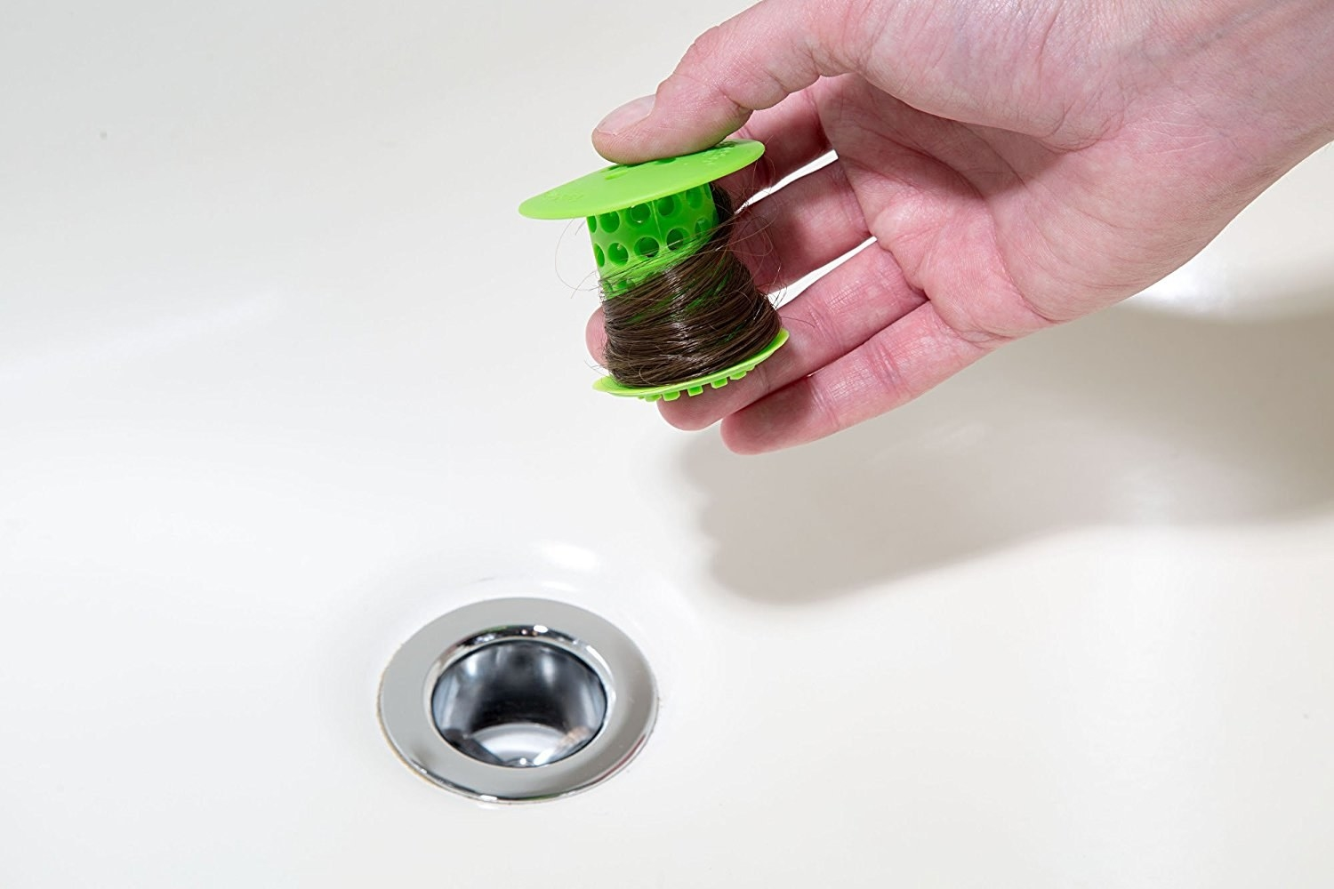 The Tubshroom in green being removed from a drain