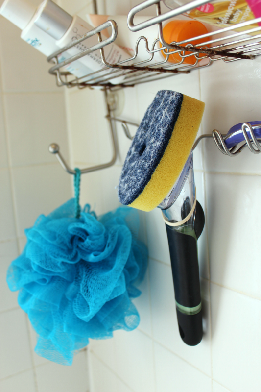 A dish brush hanging on a shower caddy between cleanings