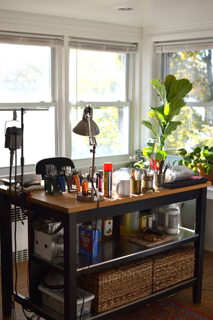 """I really enjoy my workspace because it's basically a sunroom with windows on three walls. I take advantage of all the extra sunlight and surround myself with lots of plants. Even on gray days my office feels bright, which has such an impact on my creative flow. When I'm processing orders, I usually listen to independent news podcasts, but I play something more upbeat when being creative."""