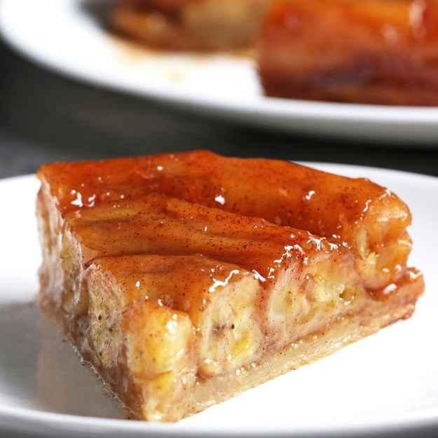 8 porçõesVocê vai precisar de: :1 folha de massa folhada, 23x23 cm6 bananas8 colheres de sopa (1 tablete) de manteiga sem sal220g (1 xícara) de açúcar mascavo1 colher de chá de baunilha1 colher de chá de canela sorvete de baunilha, para acompanharModo de preparo: :1. Preaqueça o forno a 190ºC.2. Usando uma forma de bolo redonda de 20 cm, corte um círculo na massa folhada. Usando um garfo, faça furos em toda massa para fornecer ventilação. Deixe de lado.4. Corte as extremidades das bananas e em seguida corte 2 das bananas transversalmente e deixe de lado.5. Numa caçarola grande em fogo médio, derreta a manteiga, acrescente o açúcar mascavo e cozinhe cerca de 5 minutos até que esteja completamente incorporado e a calda de cor amarelada.6. Acrescente a baunilha e a canela. Misture até ficar bem homogêneo.7. Acrescente as bananas na panela e cozinhe por 2 minutos até ficarem moles.8. Vire as bananas para cobri-las por inteiro com o caramelo, e em seguida retire da panela. Separe o caramelo.9. Unte a forma de bolo. Organize as bananas no fundo da forma. Despeje a calda de caramelo.10. Cubra as bananas com o círculo de massa folhada e certifique-se de que as bordas estejam ensacadas na forma.11. Leve ao forno por 30 minutos, ou até que a massa fique inchada e dourada.12. Deixe esfriar em temperatura ambiente por pelo menos 30 minutos antes de inverter em um prato de bolo.13. Corte e sirva com sorvete de baunilha.14. Saboreie!Inspirado por:https://www.marthastewart.com/344189/banana-tarte-tatin