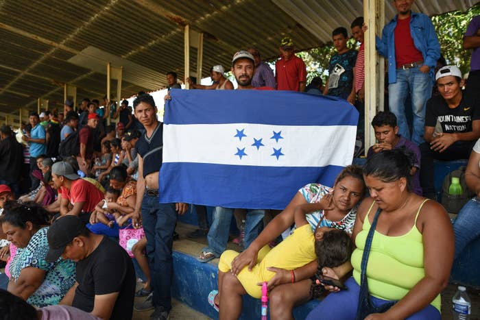 """A man holds a Honduran national flag as Central Americans — taking part in a caravan called """"Migrant Viacrucis"""" — rest in Matías Romero, Oaxaca state, Mexico, on April 2."""