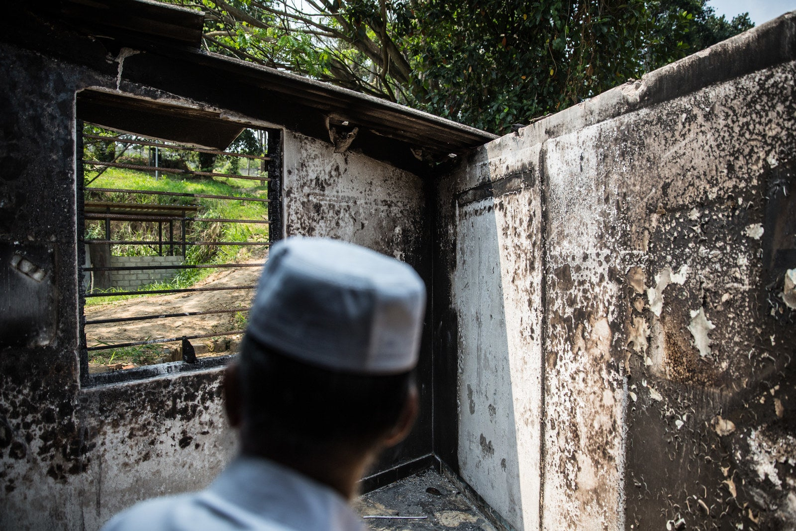 A man looks out of a burned out window at Masjidul Lafir Jummah Mosque in Digana. The attacks there were carried out by Buddhist mobs only a few weeks earlier on March 7, leaving many homes and shops destroyed and one young man dead.