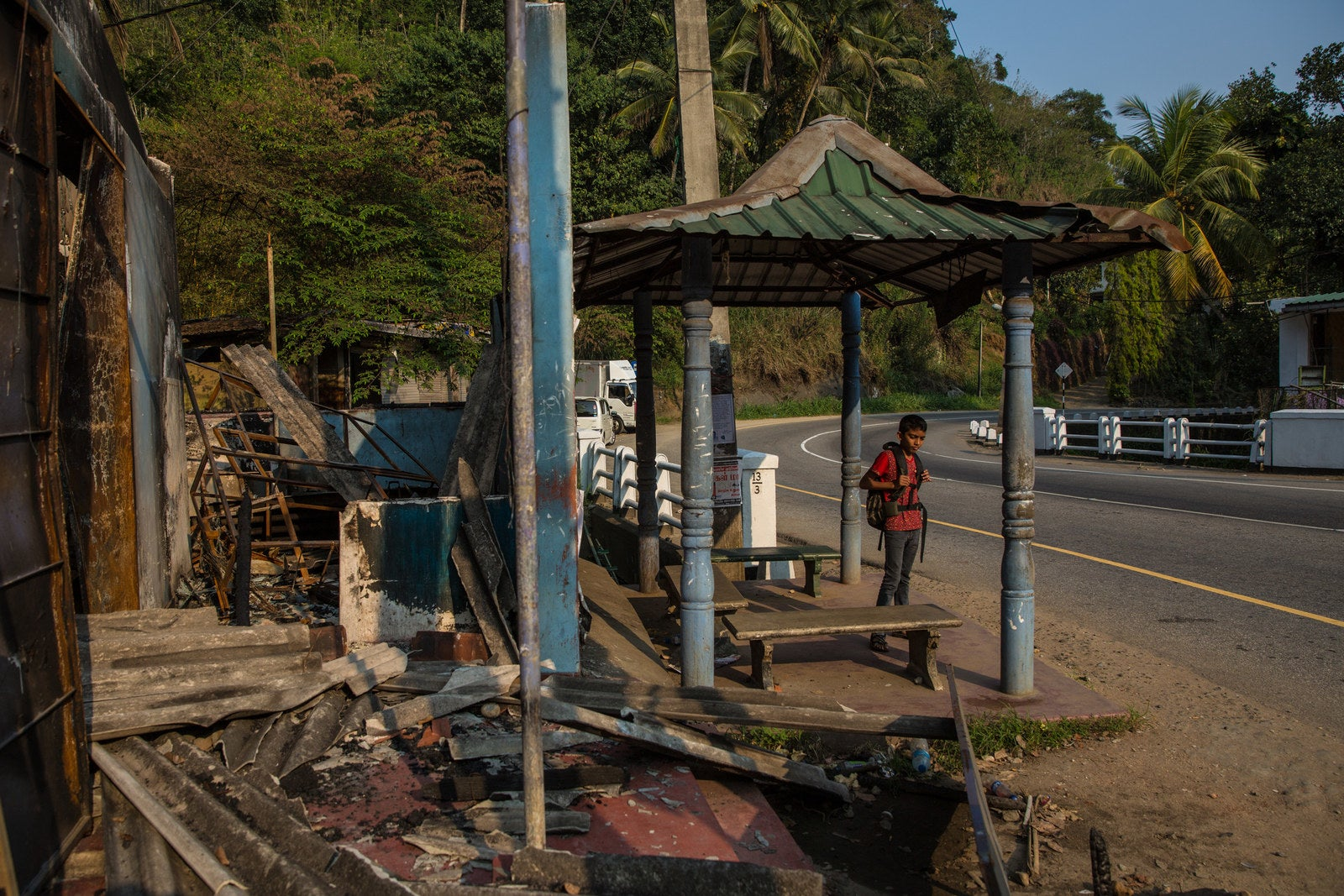 A young boy waits at a bus stop in front of a destroyed vegetable shop in Eighth Mile Post.