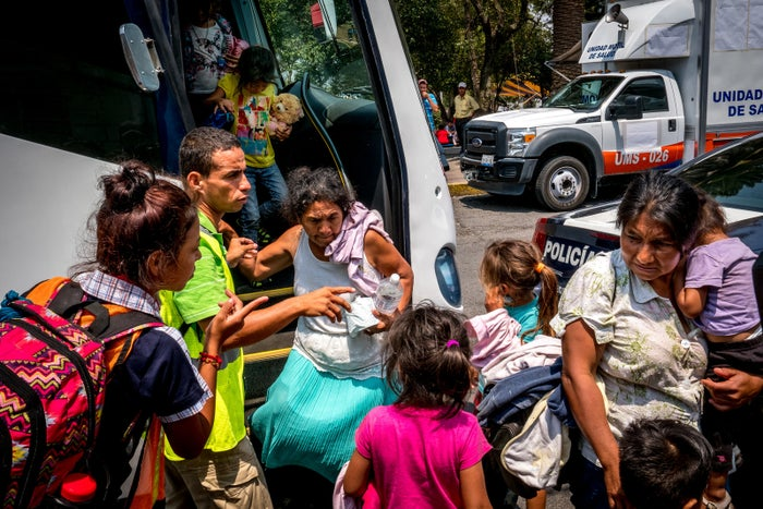 Migrants disembark from buses in Puebla.
