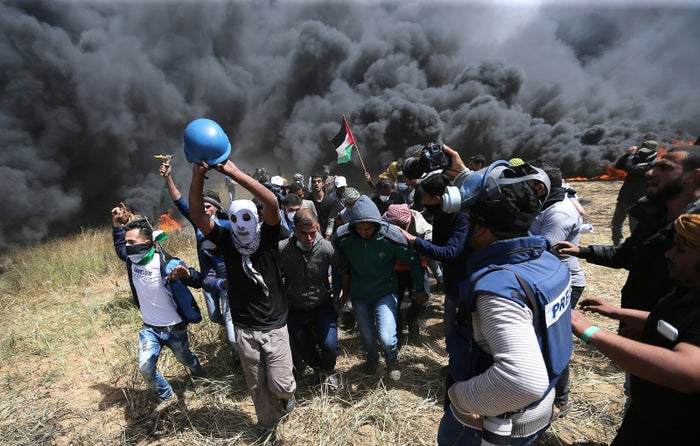 Palestinians evacuate the mortally wounded Palestinian journalist.