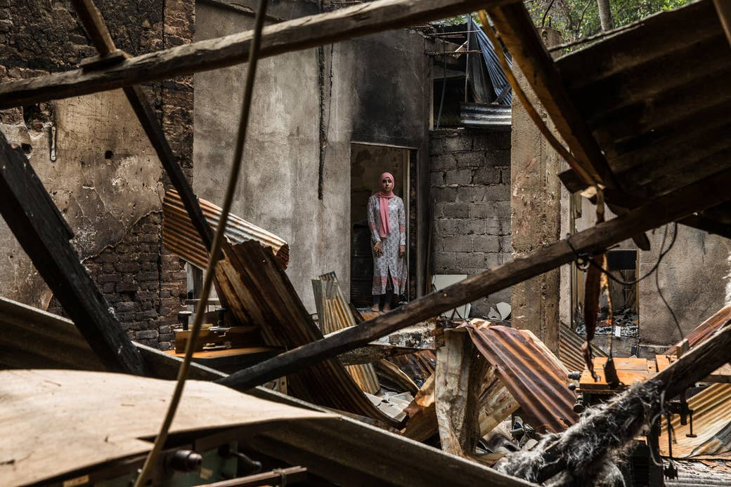 Zainab Hilmy stands for a portrait in the wreckage of her family's furniture store at Eighth Mile Post, Akurana, Sri Lanka, on March 23.