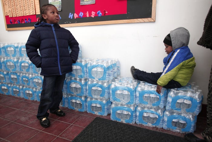 Two boys in Flint wait on a stack of bottled water at a 2016 rally about the city's lead contamination.
