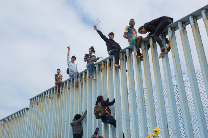 Migrants and activists scale the border wall in Tijuana during a rally for the caravan of migrants about to request asylum.