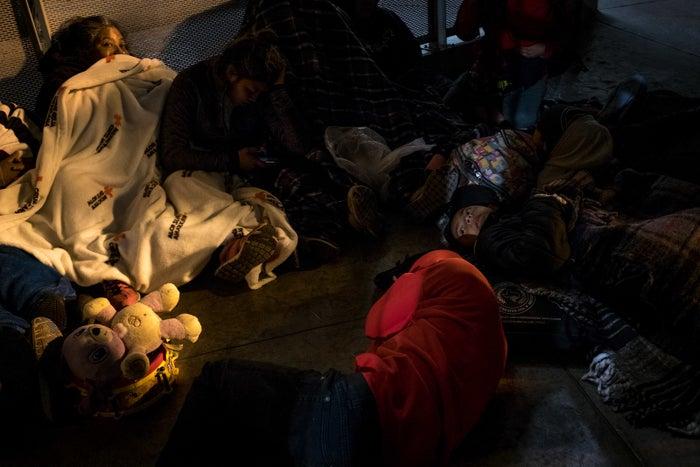Asylum-seekers sleep on the floor in a holding area.