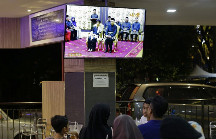 People in Kuala Lumpur watch TV showing footage of Mahathir Mohamad being sworn in as the new Malaysian Prime Minister.