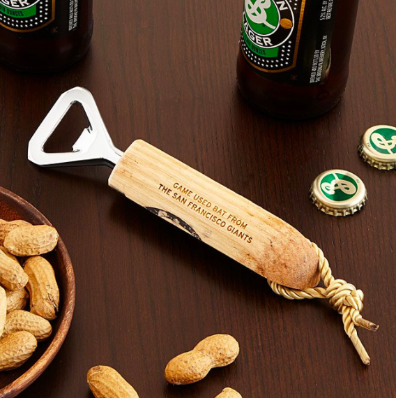A bottle opener made from the bottom of a baseball bat, with a rope attachment for hanging and an inscription of the team who used the bat