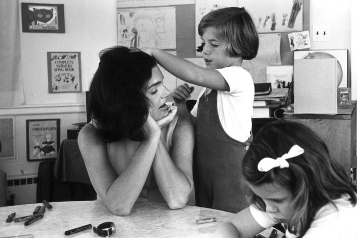 First lady Jacqueline Kennedy sits at a classroom table as her daughter, Caroline, runs her hand through her mother's hair during a visit to Caroline's school on May 24, 1962.
