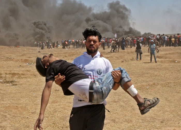 A Palestinian carries an injured protester during clashes with Israeli forces near the border between the Gaza strip and Israel east of Gaza City on May 14, 2018.