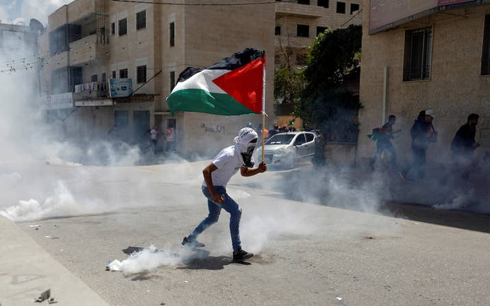 A demonstrator holding a Palestinian flag runs from tear gas fired by Israeli troops during a protest against U.S. embassy move to Jerusalem and ahead of the 70th anniversary of Nakba, near Israeli Qalandia checkpoint near Ramallah in the occupied West Bank