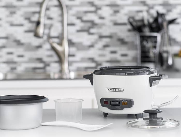 small rice cooker with plastic cup, lid, and rice spatula