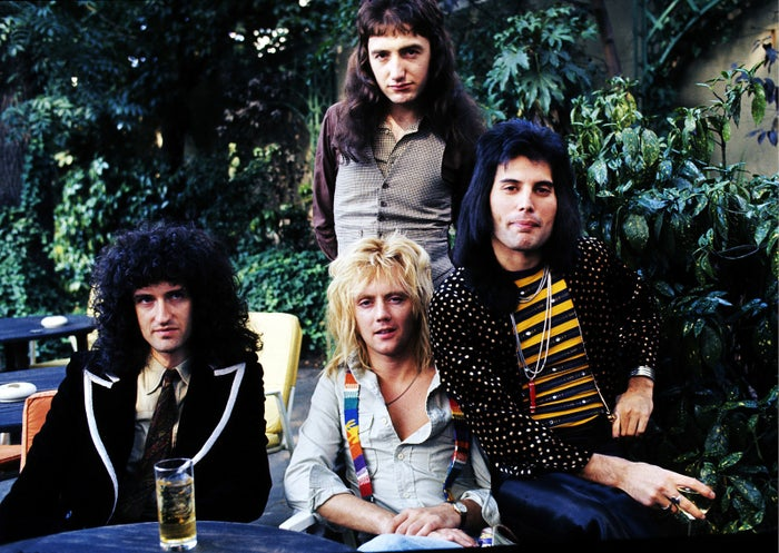 "Brian May (left), John Deacon (standing), Roger Taylor, and Freddie Mercury of Queen, sit for a portrait before being presented with silver, gold, and platinum discs for sales in excess of 1 million for their hit single ""Bohemian Rhapsody,"" on Sept. 8, 1976, in London."