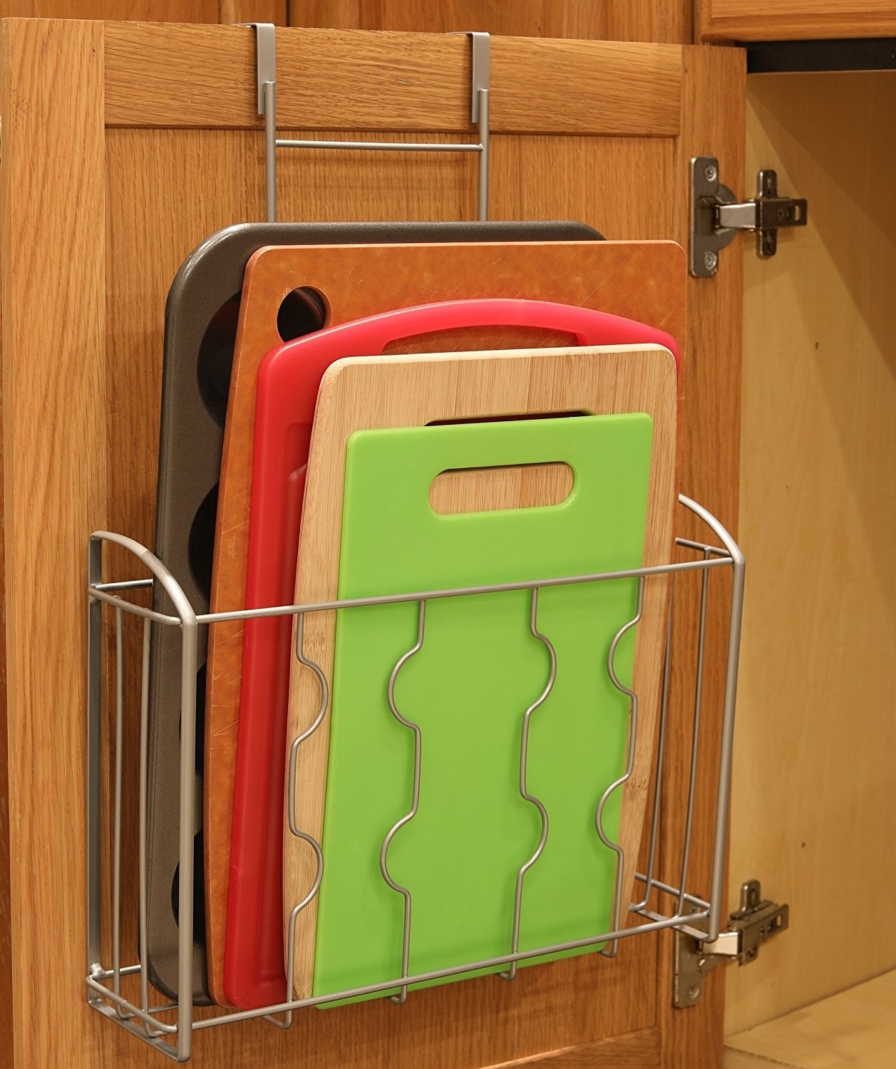 The silver wire rack hanging on a cabinet door with cutting boards and a muffin tray in it.