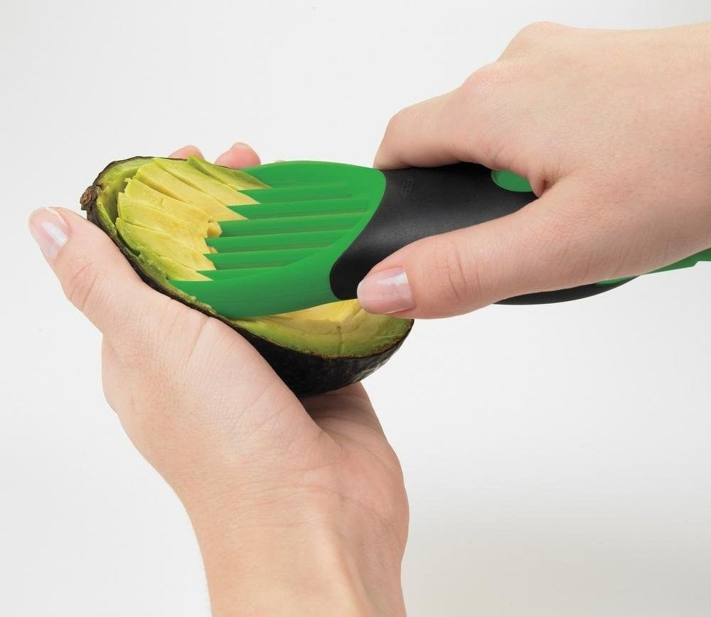 person using the tool to slice open half of an avocado