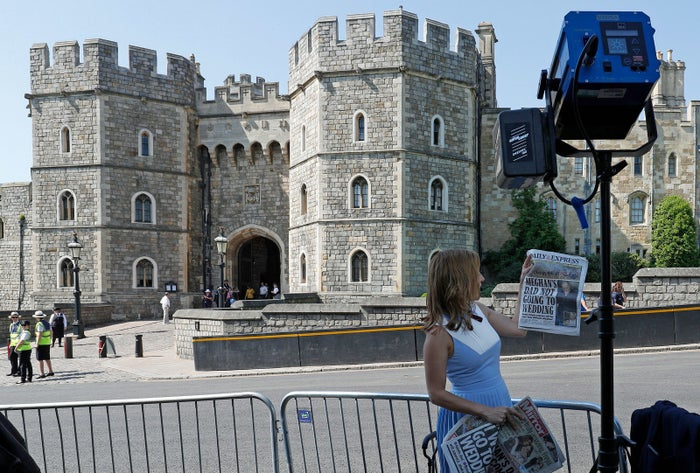 A CNN reporter holds UK newspapers with the latest Thomas Markle headlines in front of Windsor castle.