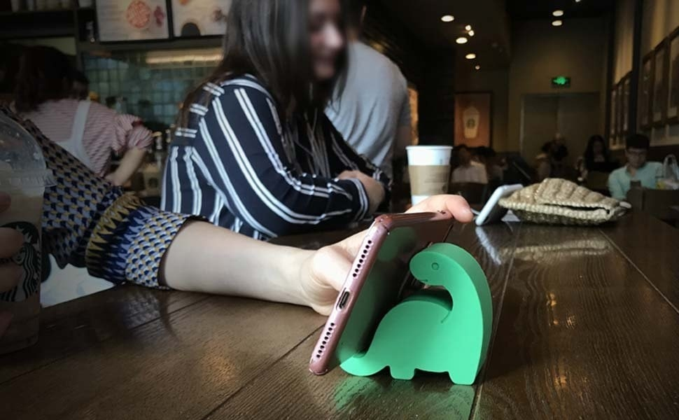 person with phone leaning up against a dino-shaped stand on a table at a coffee shop